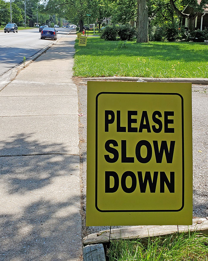 "A series of ""slow down"" signs are in lawns along the 1400 block of 183rd Street in Homewood on Saturday, July 25. (Eric Crump/H-F Chronicle)"