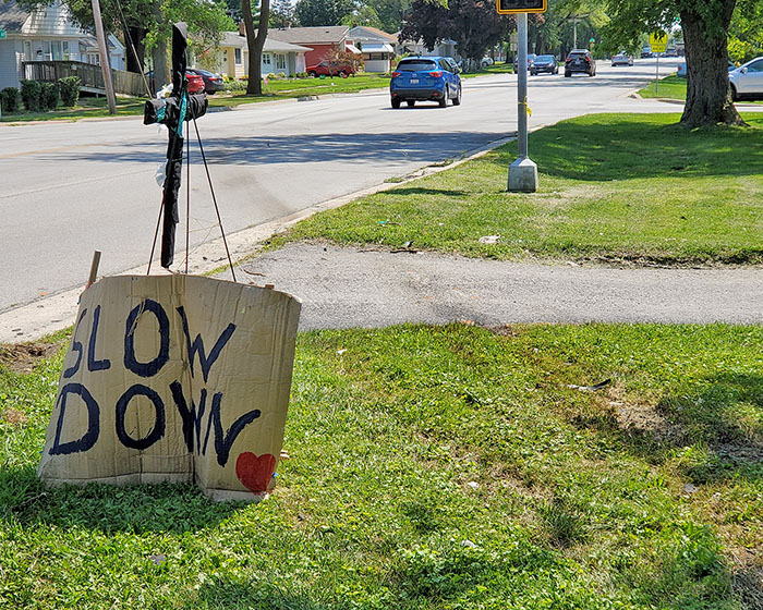 """A cross memorial and hand-made """"slow down"""" sign posted at the site of a July 22 fatal crash near the intersection of Center Avenue and 183rd Street in Homewood. To the right of the sign are grooves in the turf made by two cars sliding off the roadway after colliding in the intersection. (Eric Crump/H-F Chronicle)"""