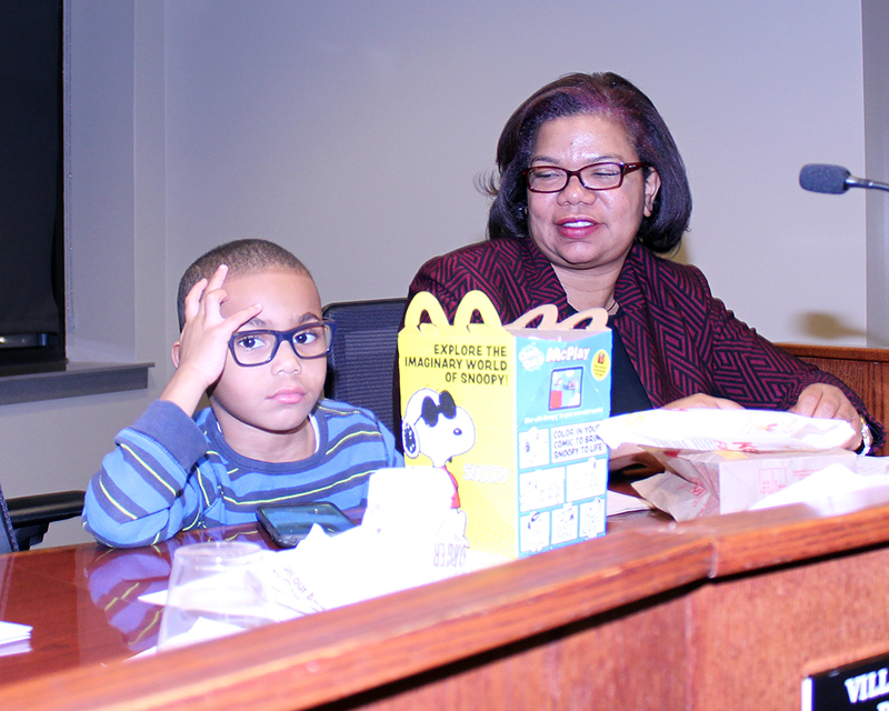 Giles Hardison briefly joins his mom, Barbara Dawkins, on the dais before a Homewood board meeting. (Eric Crump/H-F Chronicle)