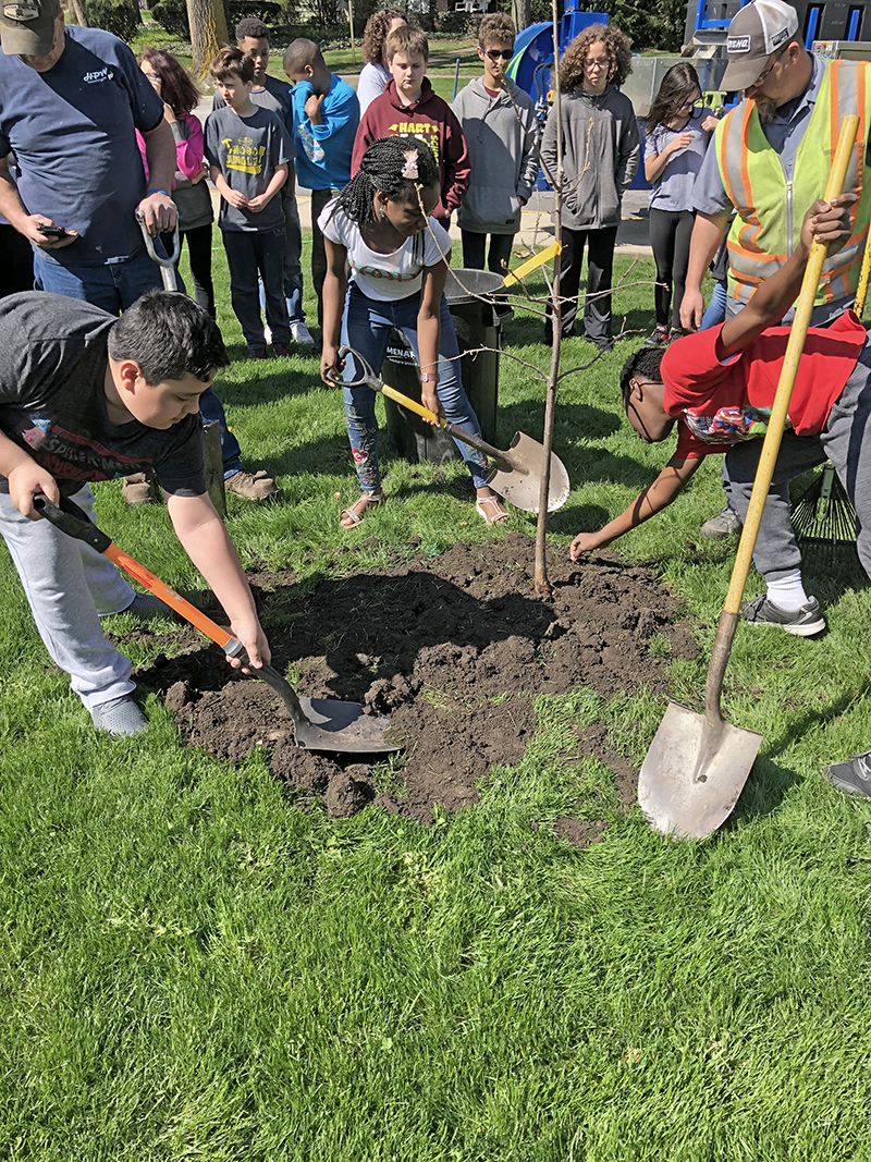 James Hart students, from Left, Joey Heredia, Blessing Simon and Kaden Chinwah pitched in to plant a tree in from of the school during an Arbor Day celebration Friday. (Marilyn Thomas/H-F Chronicle)