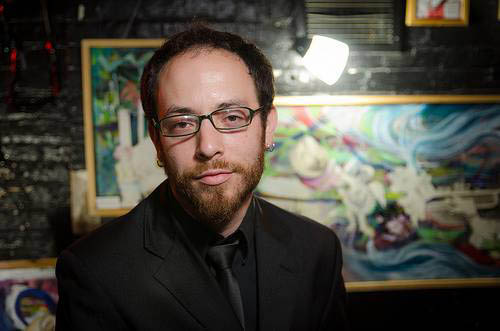 Ben Salus with his artwork in the background. (Provided photo)