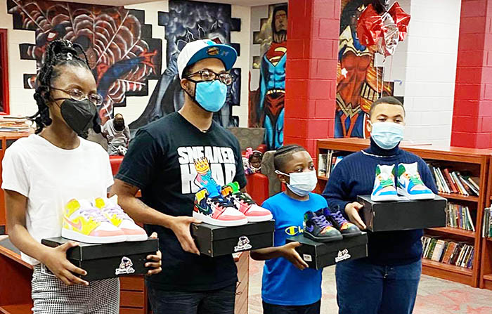 From left, winners of the sneaker design contest at Jesse White Learning Academy are Danielle Moore, Eric Rockett and Deangelo Jones. Second from left is Anthony Amos, who worked with Homewood artist Ben Salus on the sneaker design project. (Provided photo)