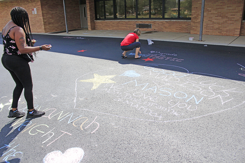Ebonie Hall steps back to check her chalk greeting for her twins, Madison and Mason, to see on their first day of fourth grade.