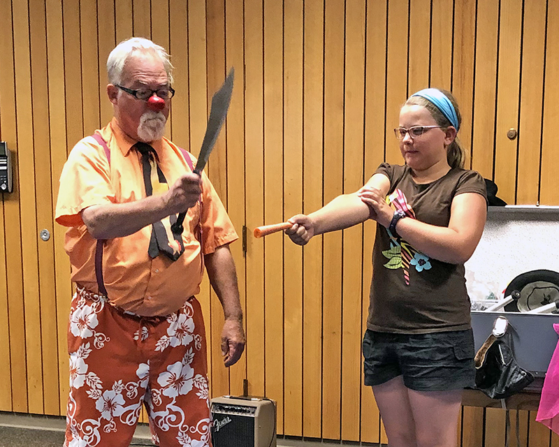 Elise Bandstra of Homewood bravely holds a carrot as Dr. Gesundheit prepares to slice off another piece during his show at the Homewood Public Library.