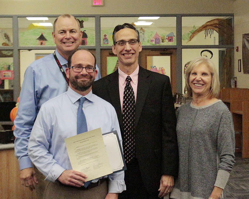From left, teacher Michael Klein, James Hart School Principal Scott McAlister and District 153 Board President Shelly Marks. Back left, District 153 Superintendent Dale Mitchell. Klein was presented with the Jerry Morin Educational Excellence Award at the Oct. 15 board meeting. (Eric Crump/H-F Chronicle)