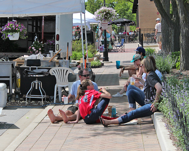 A family relaxes in the shade on opening day of the Homewood Farmers Market in 2018.