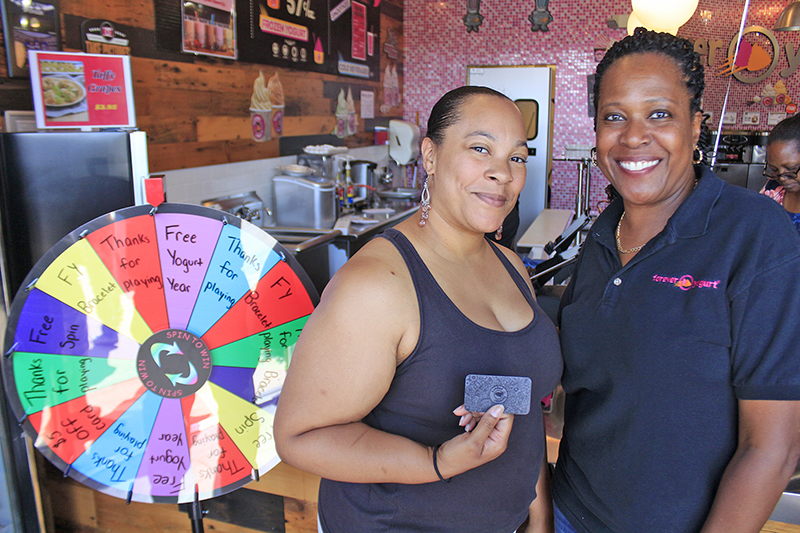 """Nicole Cornelius with Forever Yogurt co-owner Josette Fourte. Cornelius was the first up for the """"Spin to Win"""" game and was rewarded with free yogurt for a year. (Eric Crump/H-F Chronicle)"""