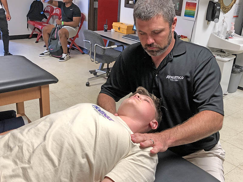 Athletic trainer Brad Kleine works to relieve neck pain of Lucas De La Torre, a football player at H-F High.