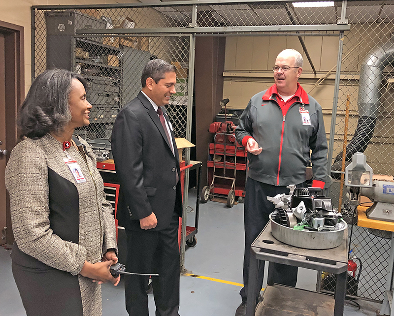 During his tour of Homewood-Flossmoor High School  with Principal Jerry Anderson, Rep. Anthony DeLuca, center, learned about the various Applied Academics programs, including the Small Engines class, from Kevin Thomas, department chair.
