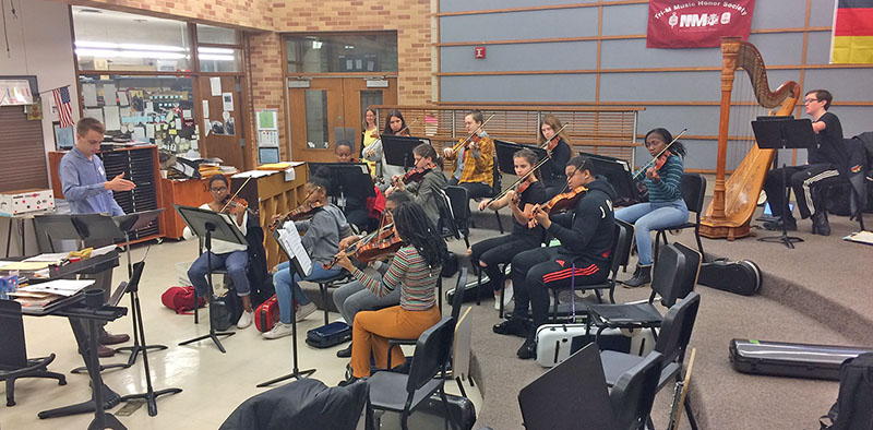Illinois Philharmonic Orchestra violinist Brian Ostrega works with members of the Homewood-Flossmoor High violin section in preparation for the Senior Conductors Concert May 21. (Provided photo)