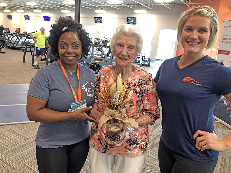 Mary Cantway, center, was presented with a special birthday gift — 105 gold dollars — by H-F Racquet & Fitness Club staff members Edy Hager, left, and Tara Lindzy, right, in honor of Cantway's 105th birthday. (Marilyn Thomas/H-F Chronicle)