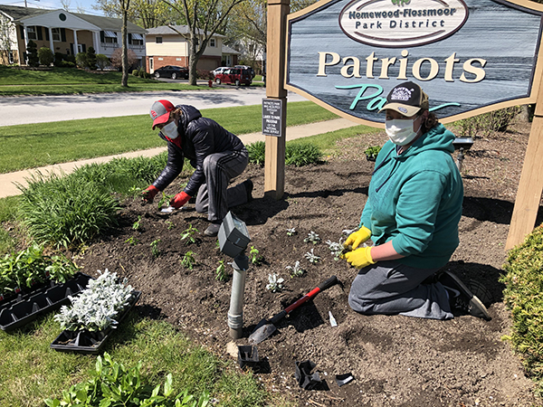 Wanda Gunter, left, and Jacqui O'Connor of Homewood took time out of their day Wednesday to plant the flower bed at Patriots Park, their neighborhood park. (Marilyn Thomas/H-F Chronicle)