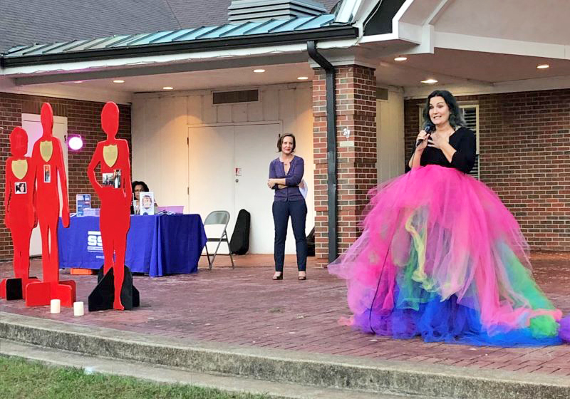 Motivational speaker Gina Bell inspires the crowd in her rainbow skirt, as South Suburban Family Shelter Executive Director Jennifer Gabrenya looks on. (Carole Sharwarko/H-F Chronicle)