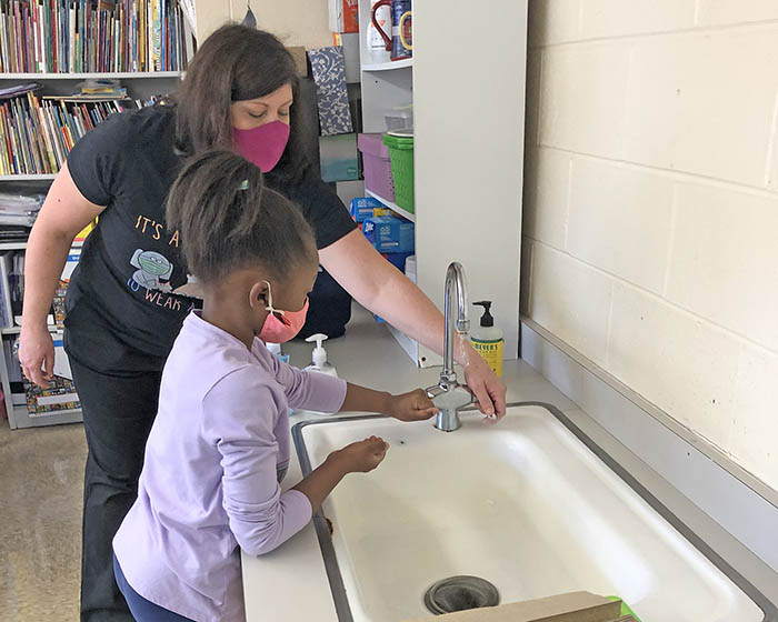 First grade teacher Margie D'Astici helps Cori Brown turn on the water so she can start her hand washing. Each student will wash their hands before starting their day. (Marilyn Thomas/H-F Chronicle)