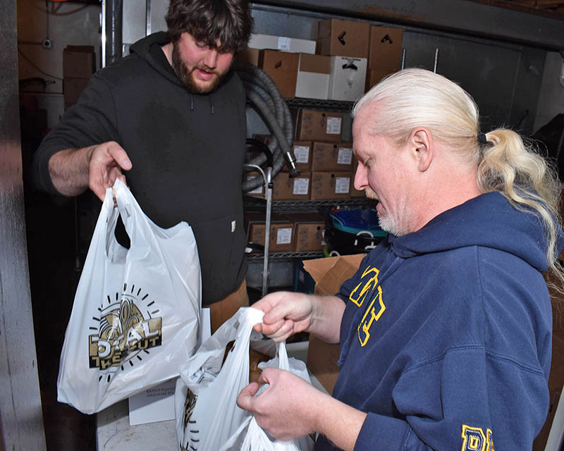 Ryan Czaja, brewmaster for Flossmoor Station, hands over bags of brew for Bob Hess. (Mary Compton/H-F Chronicle)