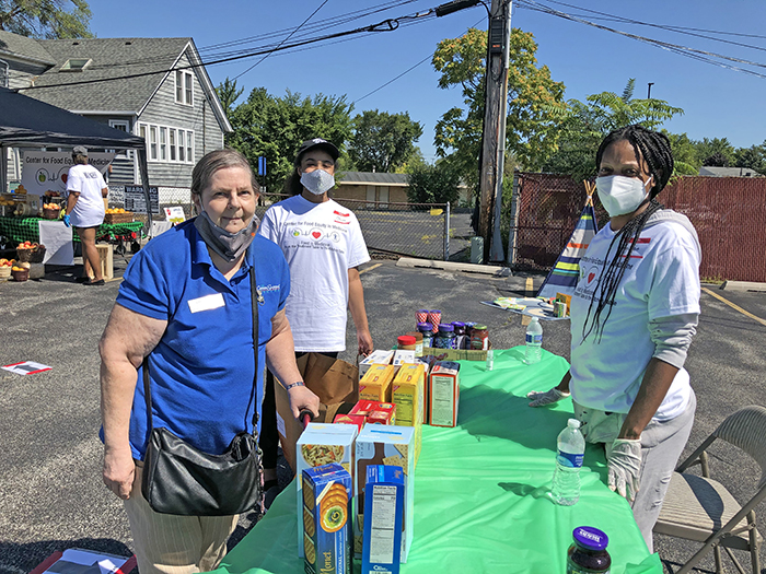 Cancer survivor Paulette Coffel of Hazel Crest, left, stops at a food station manned by Cancer Support Center volunteer Reshida Reid. Volunteer Chloe Watson, center, assists Coffel as she walks from station to station. (Marilyn Thomas/H-F Chronicle)