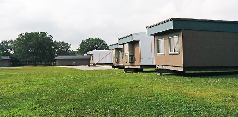 Work has begun to hook up utilities to four mobile classroom units that arrived Monday, Aug. 12, at Churchill School in Homewood. (Eric Crump/H-F Chronicle)