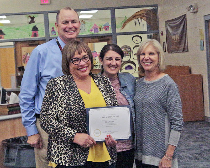 From left, teacher Deb Clark, Churchill School Principal Nikki Kerr, District 153 Board President Shelly Marks and, behind them, District 153 Superintendent Dale Mitchell. Clark was presented with the Jerry Morin Educational Excellence Award at the Oct. 15 board meeting. (Eric Crump/H-F Chronicle)