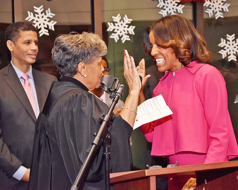 Appellate Court Judge Cynthia Cobbs, left, swears in Donna Miller as Cook County Commissioner for the 6th District, which includes parts of Homewood and Flossmoor. Looking on is Miller's husband, Dr. David Miller. (Mary Compton/H-F Chronicle)