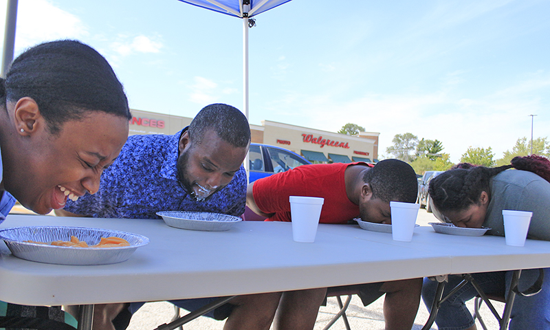 Kasayat Shokundi, left, laughs while trying to eat 11 ounces of frozen yogurt faster than her competitors, Mykel Andrews, Nnaeto Emethede and Maya Drayton. The contest was part of the fifth anniversary celebration of Forever Yogurt in the Cherry Hills shopping center. (Eric Crump/H-F Chronicle)