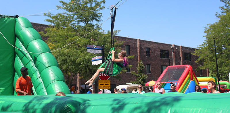 A girl cruises along on a zip line at Homewood's Giant Block Party in 2017. The event this year will again feature a number of fun activities for kids. (Chronicle file photo)