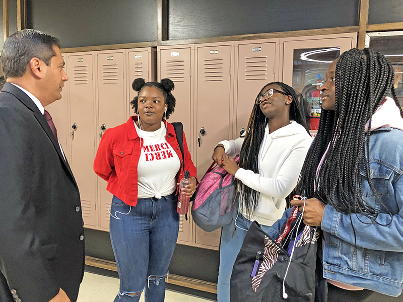Rep. Anthony DeLuca, D-Chicago Heights, got an early morning greeting from Homewood-Flossmoor High students, from left, sophomore A-Mani Evans, Salena Peebles and Jacquelyn Omodunni. (Marilyn Thomas/H-F Chronicle)