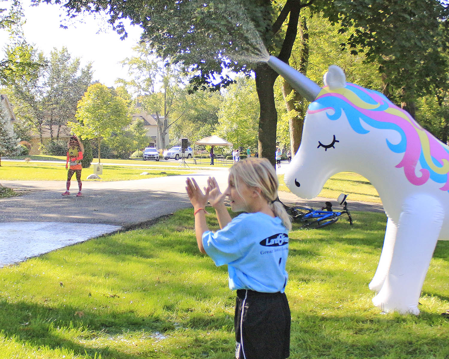 Georgia Bruni claps as runners pass her home during the 2019 Hidden Gem Half Marathon. She and her mom, Jeanette Bruni, set up a unicorn water spray to cool off runners. (Chronicle file photo)