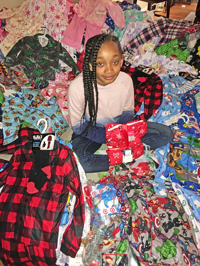 Ten-year-old Homewood resident Dannen Rose sits among some of the 300 pairs of pajamas she helped collect for patients at Lurie Children's Hospital. (Carole Sharwarko/HF Chronicle)