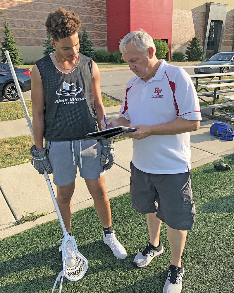 H-F High player Malcolm Grant listens as lacrosse coach Mark Thompson plots a game strategy. (Marilyn Thomas/H-F Chronicle)
