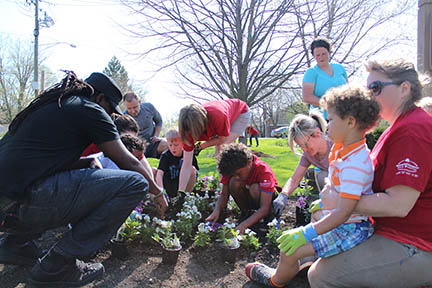 Families work together to plant colorful flowers in a bed at Heritage Park in Homewood during the 2018 Park Pride event. (Chronicle file photo)