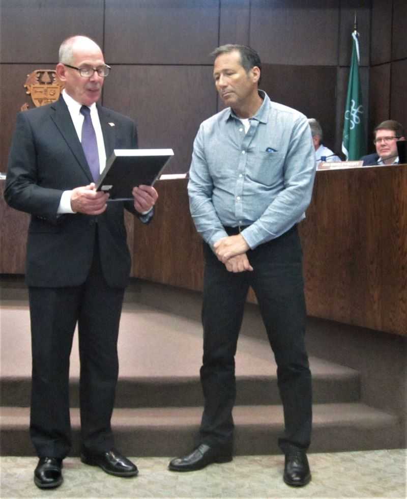 Mayor Paul Braun reads a resolution honoring Flossmoor Police Chief Mike Pulec for his service Monday, May 20. Pulec retired from the department May 17. (Stephanie Markham/H-F Chronicle)
