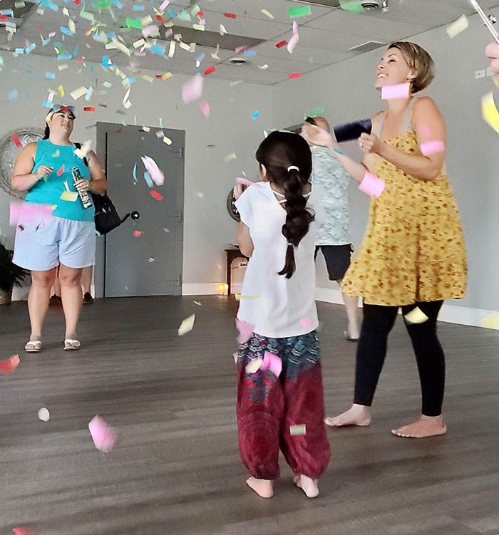 A shower of confetti marks the conclusion of the ribbon-cutting ceremony at Serendipity Yoga on Saturday, July 17. (Eric Crump/H-F Chronicle)