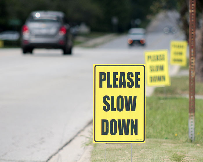 "Residents along 183rd Street and elsewhere in the community have been placing ""Please Slow Down"" signs and variations on that theme in their yards in an effort to persuade drivers to follow the posted speed limit. (Eric Crump/H-F Chronicle)"