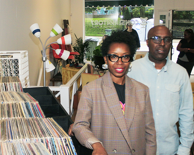 Chogie Fields, left, and Anthony Fields with the vinyl record display at The Conservatory during the store's soft opening June 21. In addition to vintage vinyl, the store includes mid-century modern furnishings. (Eric Crump/H-F Chronicle)