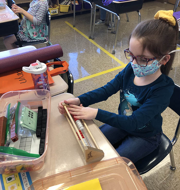 Taryn Welsh counts with an abacus that is part of her math tool kit. The first grader returned to the classroom on Monday. She and her classmates will be together mornings on the hybrid learning schedule.