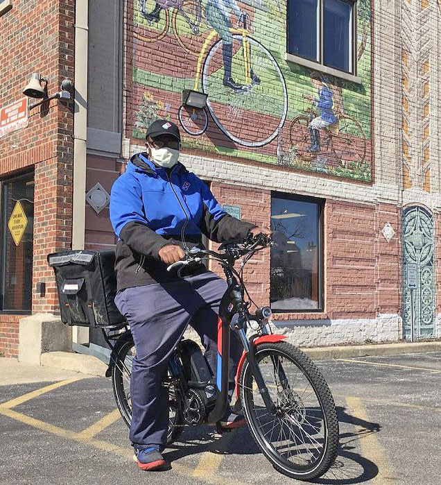 Chad Vickers, franchise owner of Domino's Pizza in Homewood, sits on an e-bike, which staff are now using to deliver pizza within a 1.5 mile radius of the store (Provided Photo)