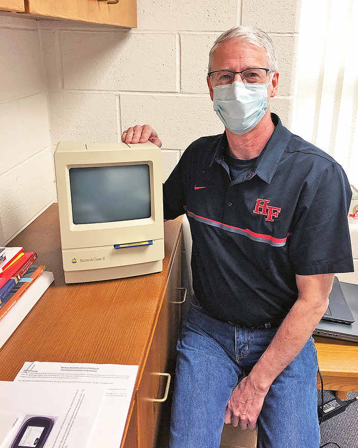 Gary Posing with one of the original Apple computers purchased by H-F's first technology director Bob Gerencher in the 1990s. (Marilyn Thomas/H-F Chronicle)