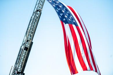 The Flossmoor Fire Department flies a large American flag in front of the station. Runners passed beneath the flag moments after leaving the starting line. (ABS)