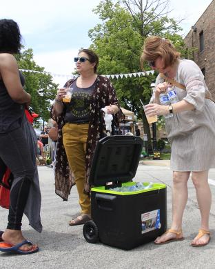 Fair curators Dodi Wians, middle, and Lisa Komorowski deliver water to vendors.