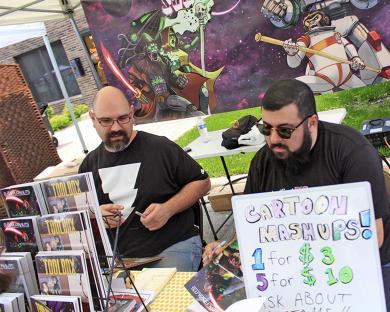 Matt Wright and Marc Alan Fishman of Unshaven Comics sign copies of their work.