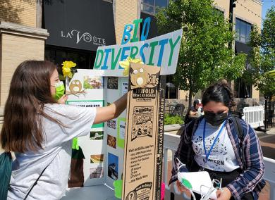 Gabby Carrillo, left, and Safa Siddiqui set up a Homewood Science Center poster display on biodiversity. (EC)