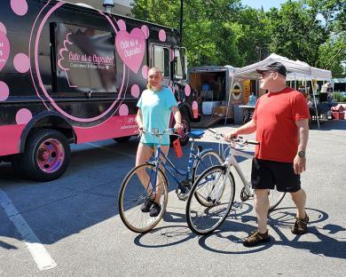 Nonita Reksisius, left, and Joe Borter of Homewood walk their bikes through the fair. (EC)