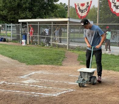 Cameron Williams, who served as home plate umpire during the championship game, paints the lines for the batter's boxes. (BJ)