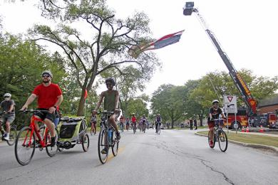 With Flossmoor Fire Department's big American flag display in the background, cyclists start the 13.1 mile Bike the Gem route. (EC)