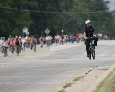 Flossmoor Police Chief Tod Kamleiter leads cyclists through the intersection of Flossmoor Road and Kedzie Avenue during Bike the Gem. (EC)