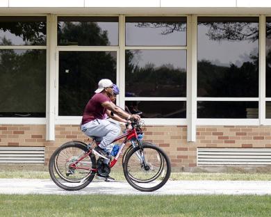 Cyclists pass the south building of Homewood-Flossmoor High School. (EC)