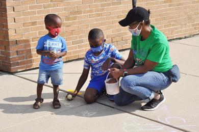 During Chalk the Walk, (left to right) Liam Nickols, 2, fourth-grader Djimon Shakoor and Kelli Nickols decorate the sidewalk outside of Heather Hill Elementary School. (BJ)