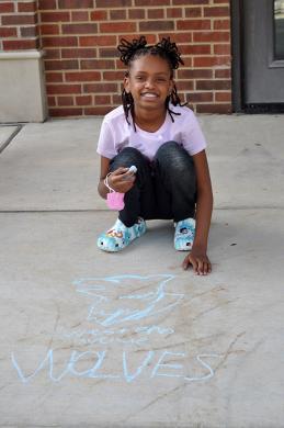 Avery Jones, 9, shows off the Wolves logo she drew near the front door of Western Avenue Elementary School. (BJ)