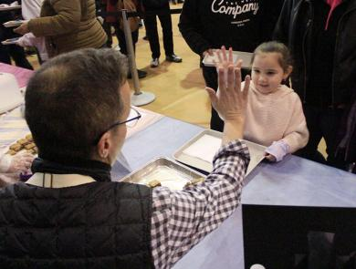 """Alani Garcia of Glenwood, who was at Chocolate Fest with her mom, Jamina Garcia, gives baker Nick Quirke a high five before receiving a """"qookie."""""""