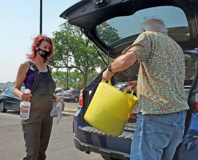 Marie Zubinski watches as Ken Cyrwus loads a bucket of compost into her vehicle. (EC)